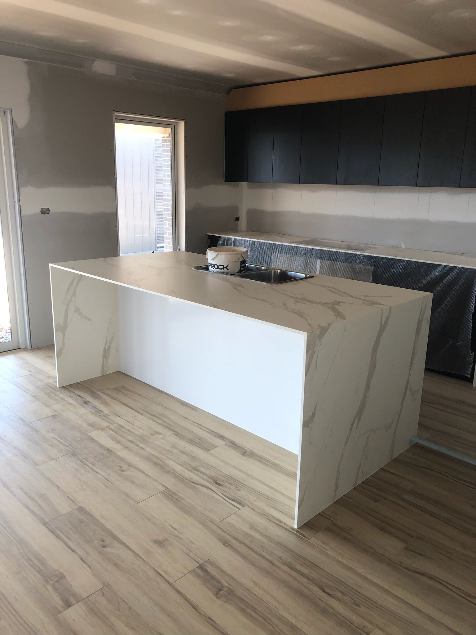Xenolith polytec benchtop with black finegrain cupboards