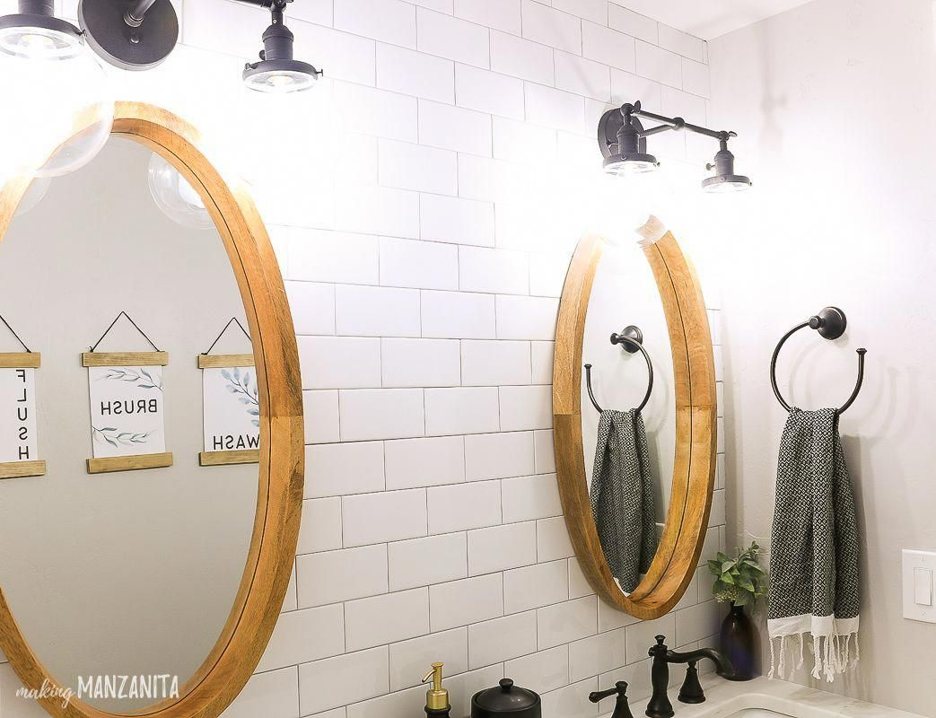 Side By Side Oval Mirror Hanging On White Subway Tile Wall With