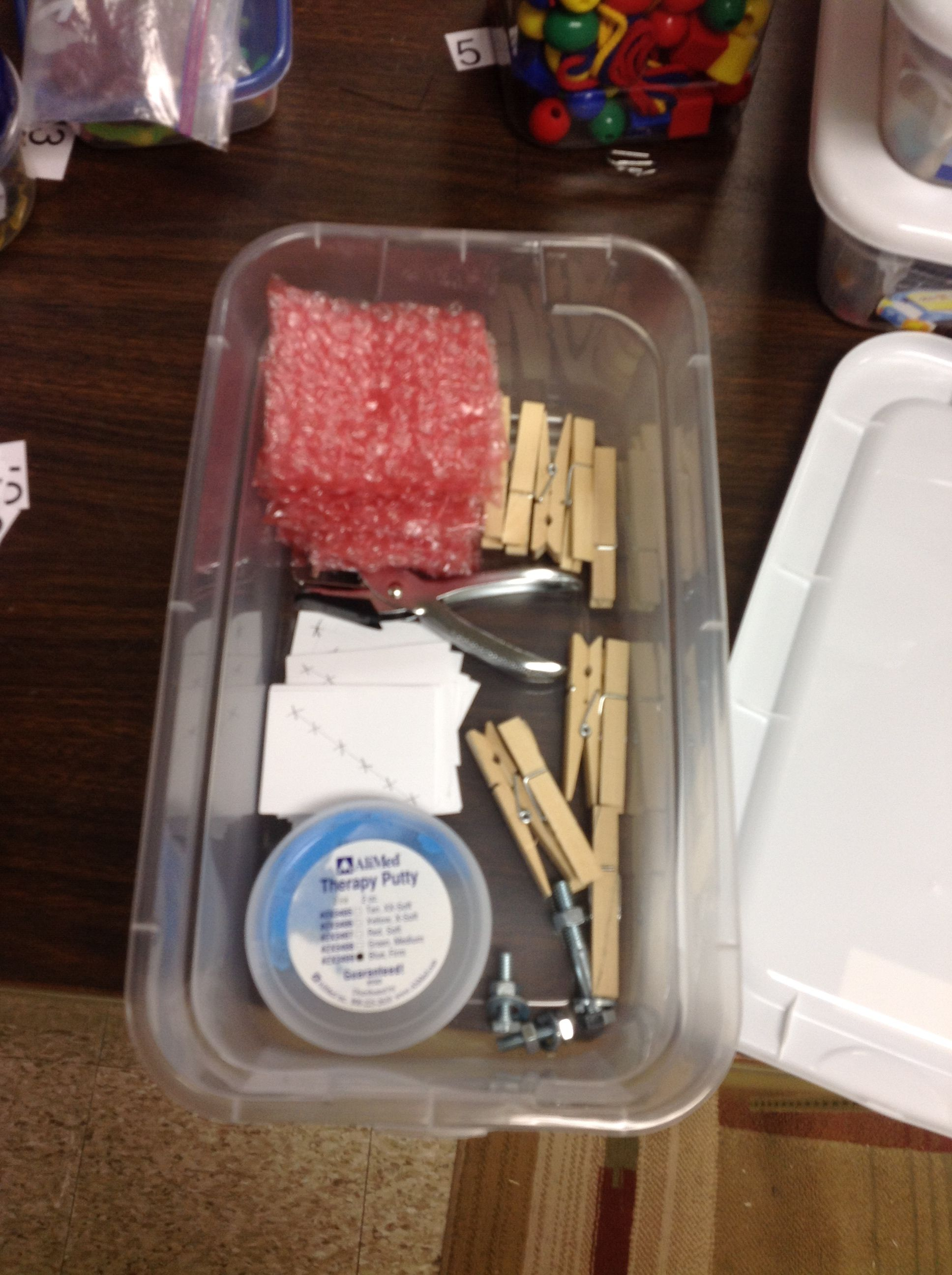 Hand Strengthening task box: includes hole punch and cards to punch out, therapy putty, clothes pins, bubble pop. Great for OT.