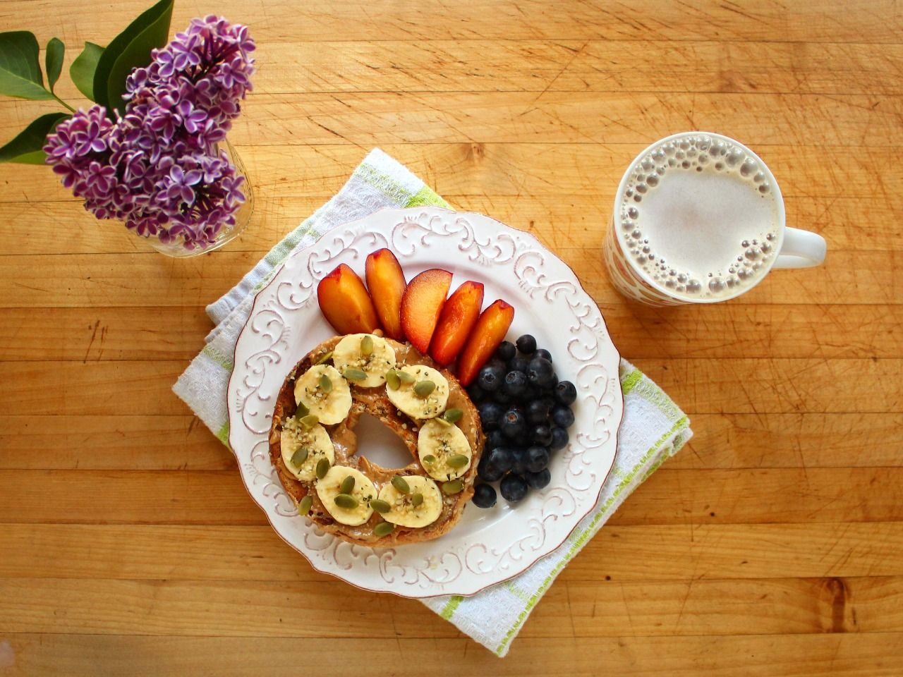 Whole grain bagel with peanut butter, banana, pumpkin seeds, and a sprinkle of hemp hearts, a sliced red plum, blueberries, and coffee with vanilla soy milk.