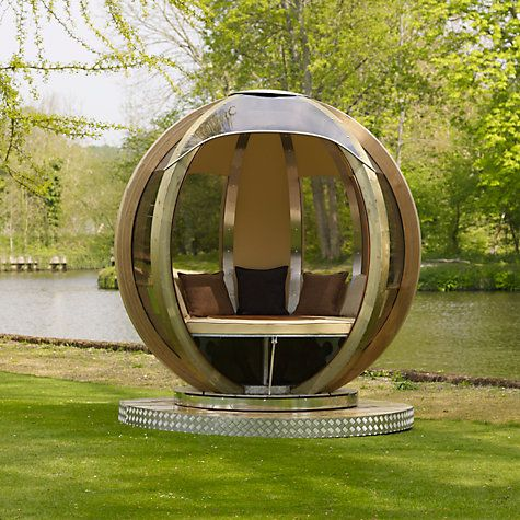 Farmer's Cottage Rotating Seated Garden Pod is part of garden Seating Pod - A new concept to the garden seating and resting environment, the rotating sphere lounger can be used for dining, relaxing, study and even a camping area, with the added advantage of rotation, to position the entrance into the sun or shade or out of a chilly wind! The earthy, waterproof interior blends perfectly with the rustic outer timbers and contains a seat and height adjustable table  When lowered to the height of the seat, the table and seat together can be formed into a full circle to make a bed, comfortably covered with a full set of luxurious, 75mm thick cushion pads  The rotating sphere lounger is made from laminated pine with UV protected polycarbonate tinted windows, protecting the inside from the elements, while allowing full, panoramic views  Mirror polished stainless steel louvres, above and below each window, reflect the surroundings and deflect heat, keeping the inside cooler in summer  The whole assembly rotates on 6 sealed chromium bearings  These run on a galvanized angle iron track, which has a stainless steel ring to to keep it running smoothly  Please note A hard standing base is required to ensure the sphere remains firmly located in position  Visit one of our shops today to experience the Rotating Sphere Lounger with one of our expert partners