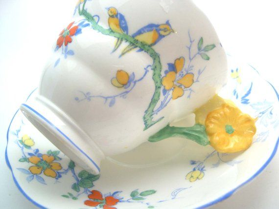 Rare tea cup and saucer from Radfords FentonModel: MacawLight yellow and green flower handle, HandpaintedThe rims are royal blue.The set was made between  1925 - 1928Cup Measures: 2 3/4