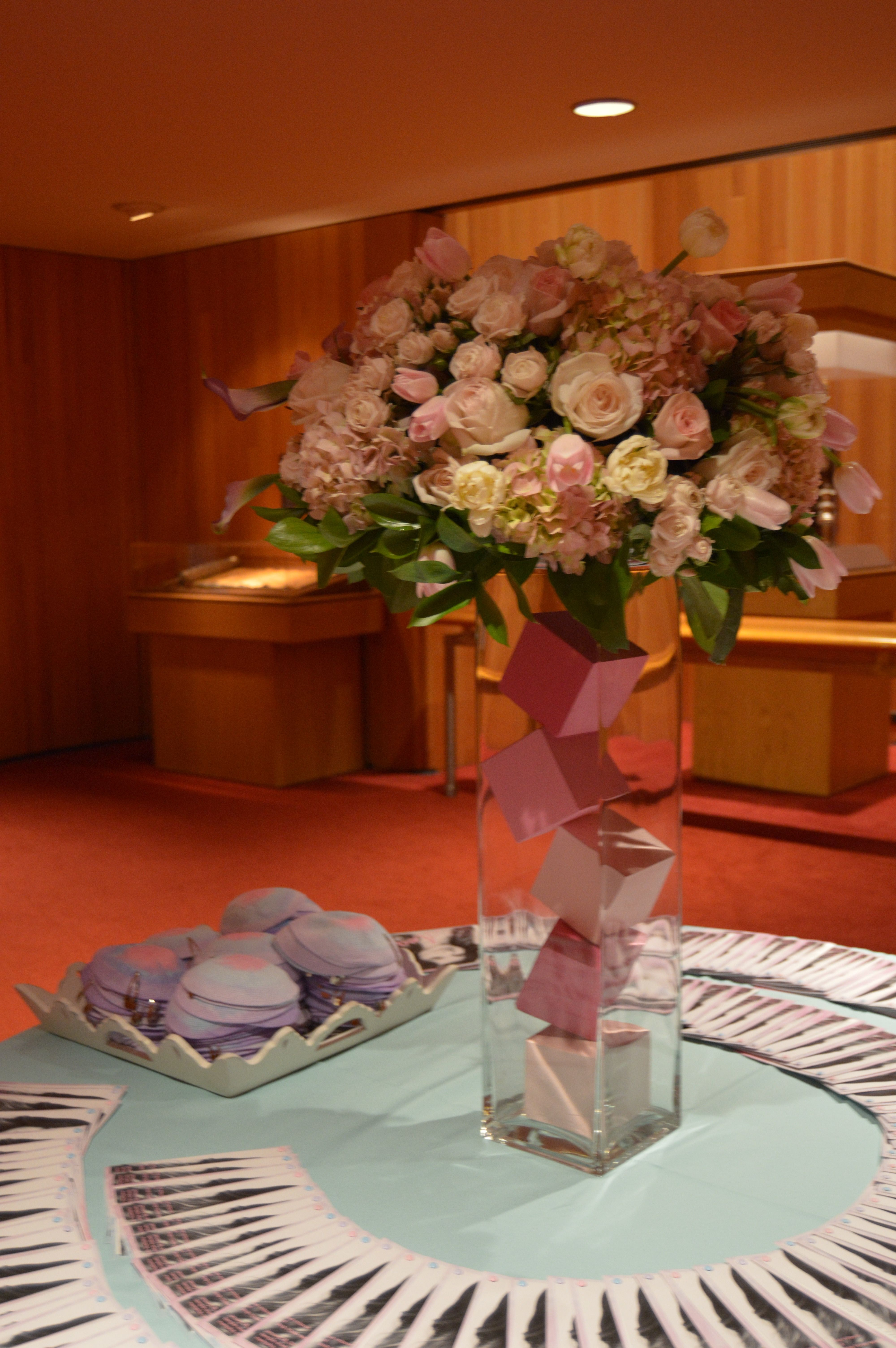 ombre pink cubes fill this clear cylinder topped with an assortment of gorgeous pink florals. Perfect kippot table arrangement