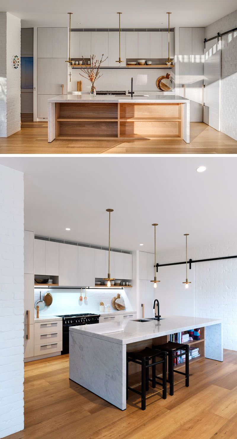 In this mostly white kitchen, the island has exposed storage and an ...