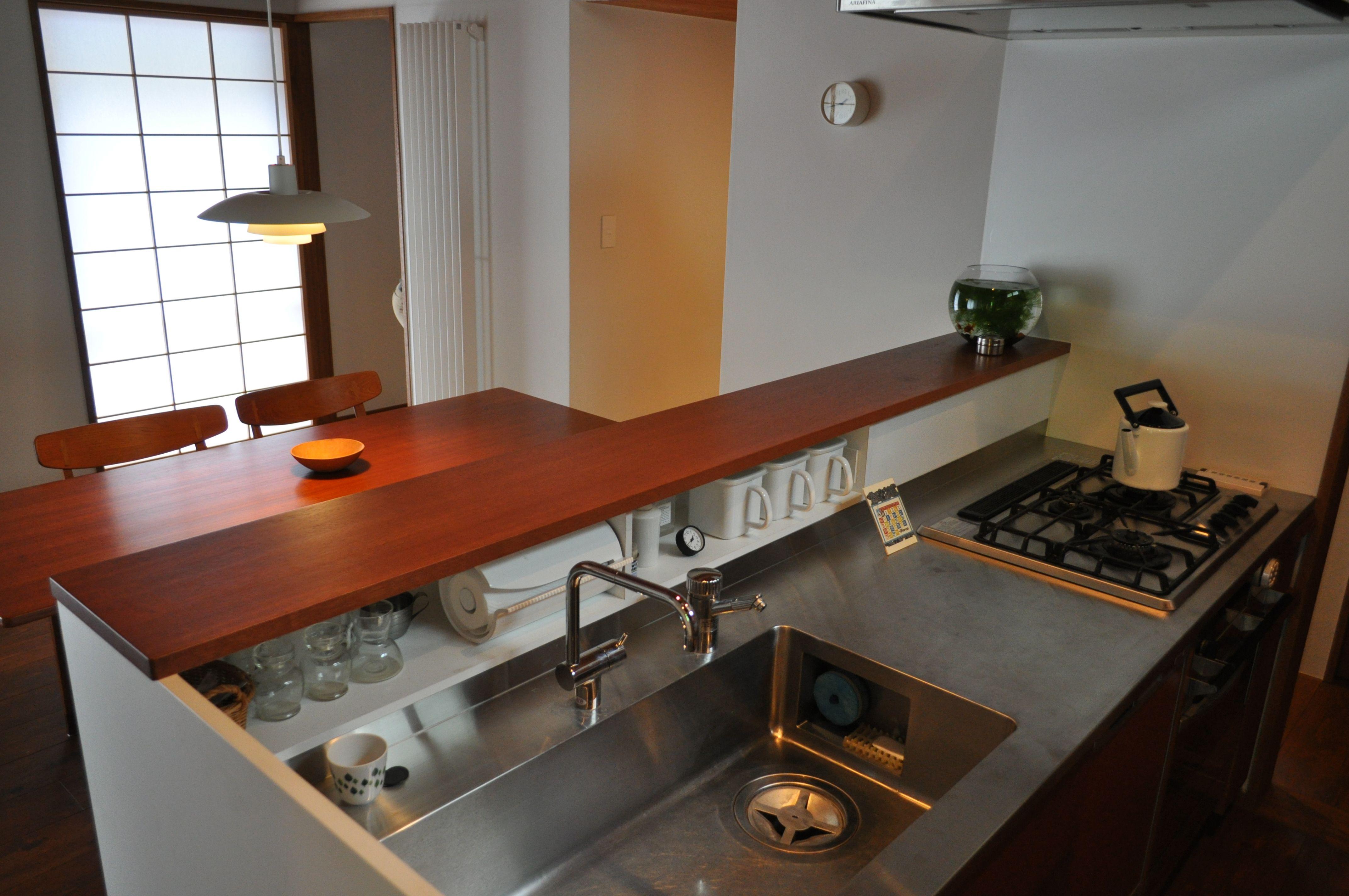ダイニングと対面するキッチン 手元が見えないように25cm程の立ち上がりを造り 上を配膳用カウンターとして使う キッチンデザイン キッチン ダイニング