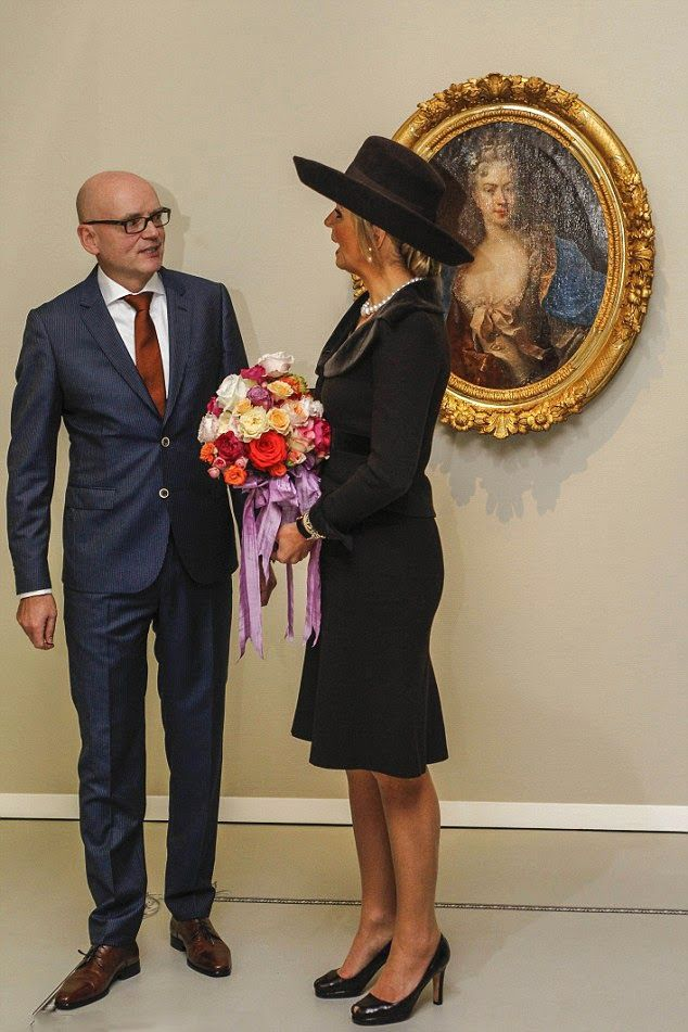 Queen Maxima dressed in a wide-brimmed brown hat that matched her brown skirt suit with chestnut velvet lapels as she met with staff from the gallery
