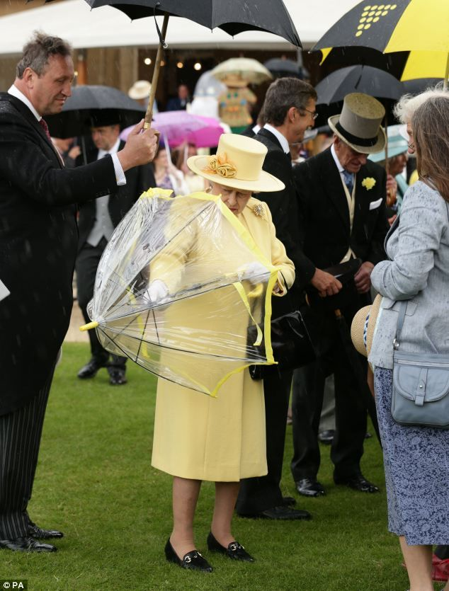Ever prepared, the royal puts up her Fulton umbrella as the rain began to fall during the celebrations 3 June 2014