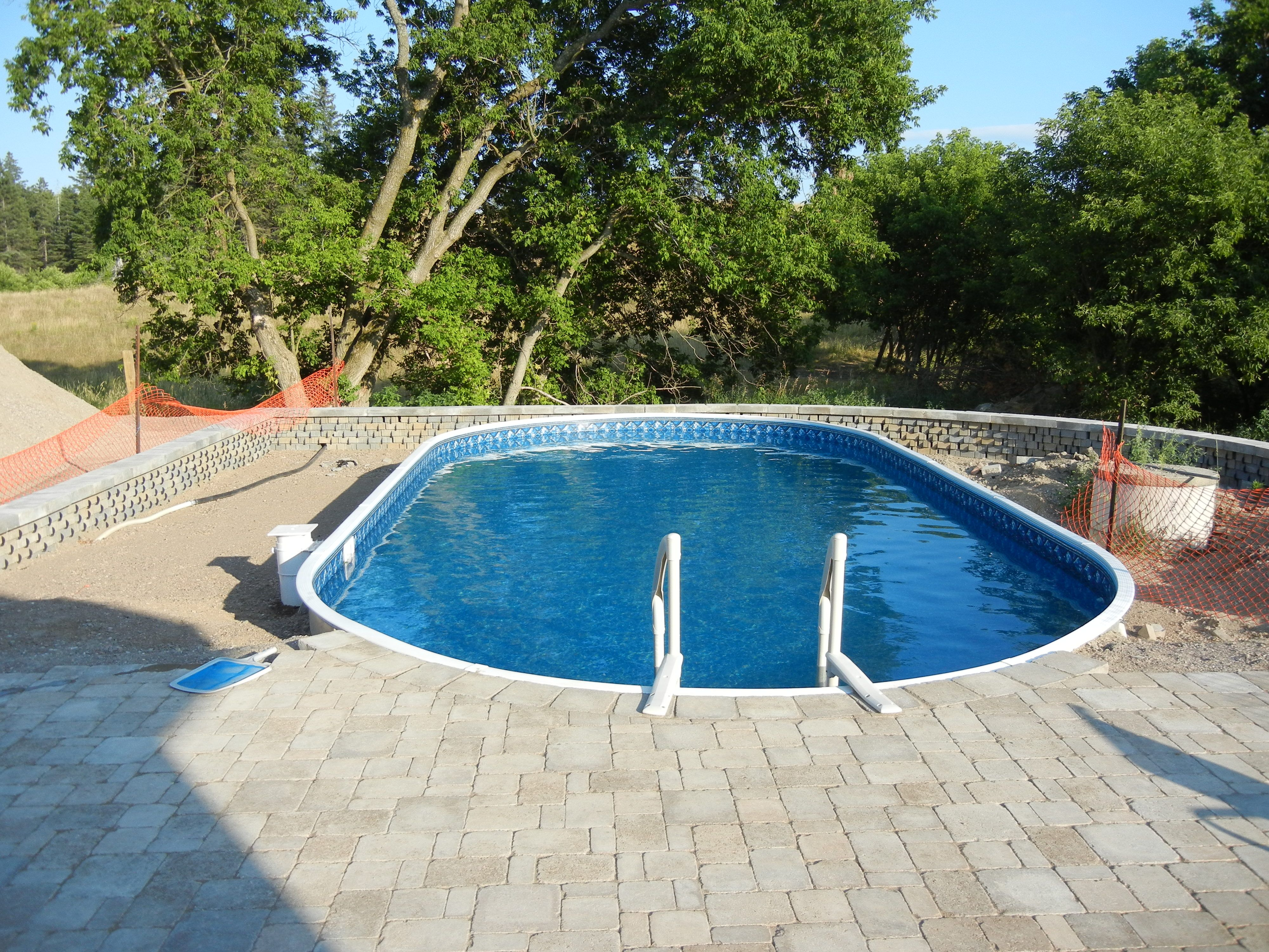 on ground pool buried all the way surrounded with square mosaic interlock