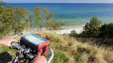 Ein Radfahrer blickt am Kap Arkona auf die Ostsee.