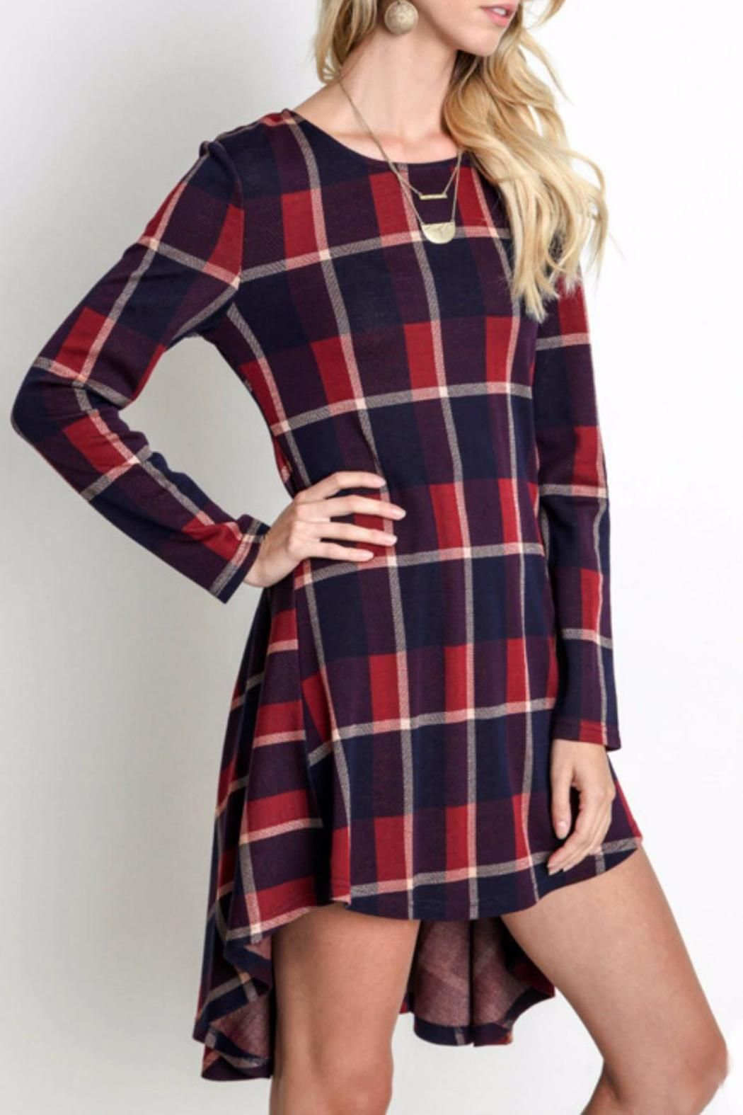 """Burgundy and navy plaid long sleeved, high-low tunic. This dress has a round neck line and has long sleeves. This dress could be worn casually with leather sandals, or with jeans and boots. It could also be dressed up with heels and sparkly jewelry. The fabric feels soft, and is sturdy enough to hold a nice shape. Measures From the top of the shoulder to the hemline the dress measures 33"""" in the front. In the back it drops as long as 36"""". The bust measures 19"""" across the front. Burgundy…"""