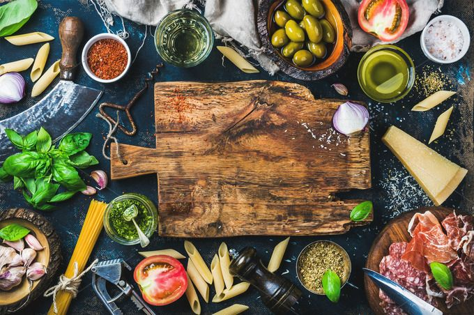 Italian Food Cooking Ingredients On Dark Background With Rustic Wooden Chopping Board In Center Top View Copy Space