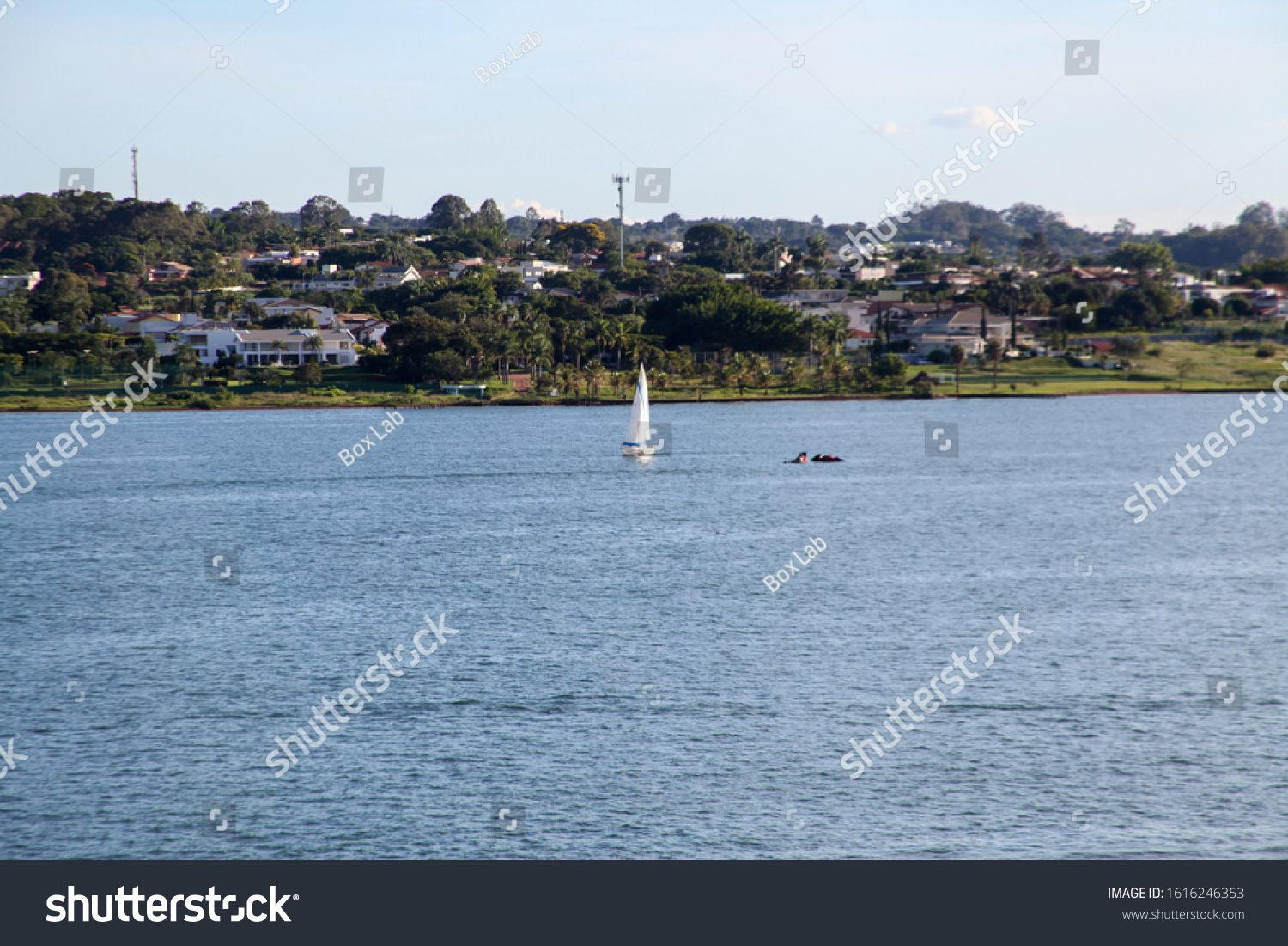 A sailboat on Lake Paranoa, an artificial lake formed by the dammed waters of the Parano¨¢ River. Incredible view with leisure and water sports options. In the background a condominium with houses #Ad , #Ad, #dammed#formed#Parano#waters