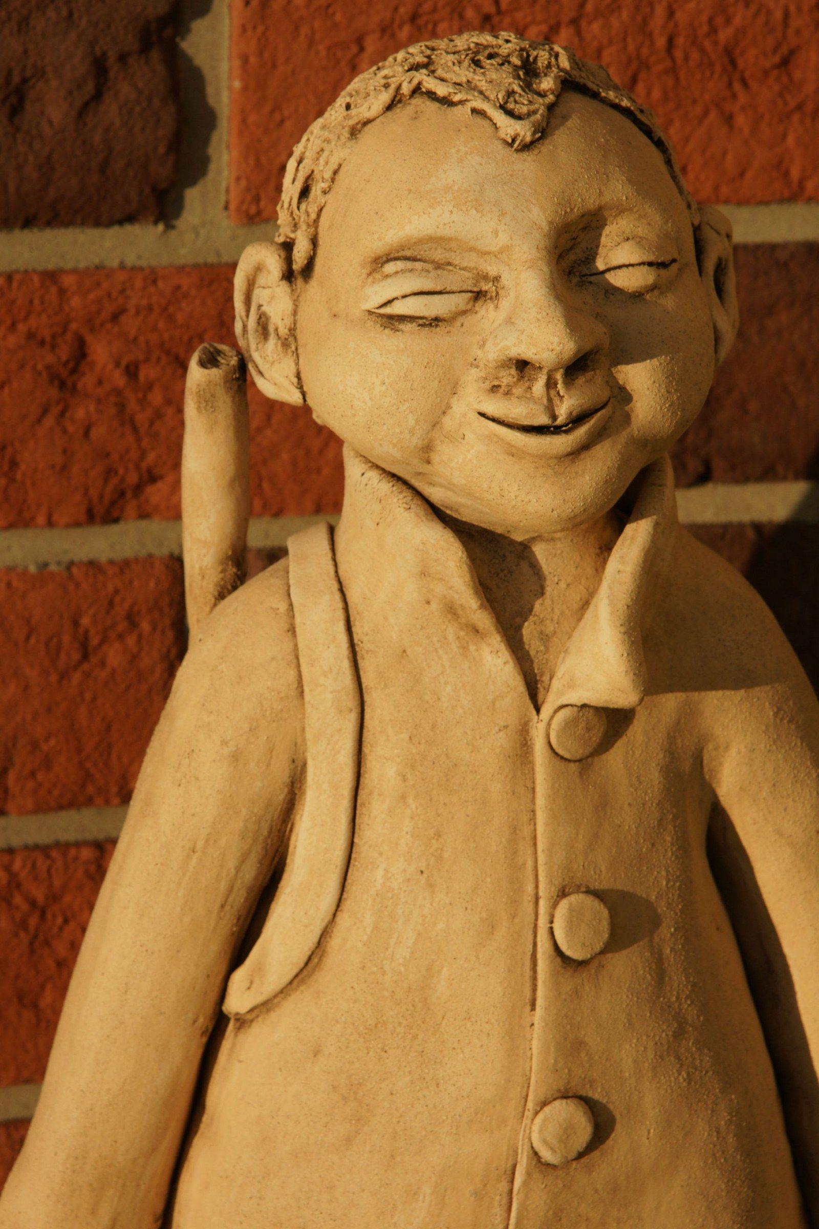 Myslivec Velká soška myslivce modelovaná ze šamotové hlíny, přes rameno má pušku a na výšku 50cm
