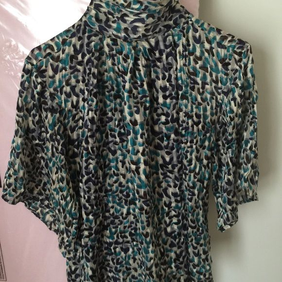 Leopard Turtlneck blouse Shirt is a chiffon material. Very classy I wore with pearls earrings and a black pencil skirt very sophisticated look. The coolest part is the blue button going up the neckline in the back! Very good condition Classiques Tops Blouses