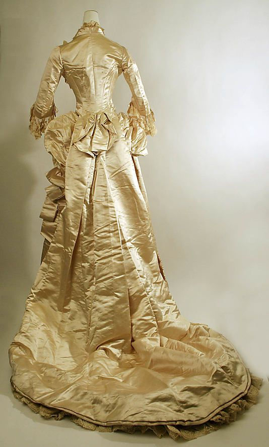 Wedding ensemble from 1885.  Beautiful ivory silk gown trimmed in every imaginable frill possible:  lace, glass pearls, ruffles, bustle & train.  Wow!