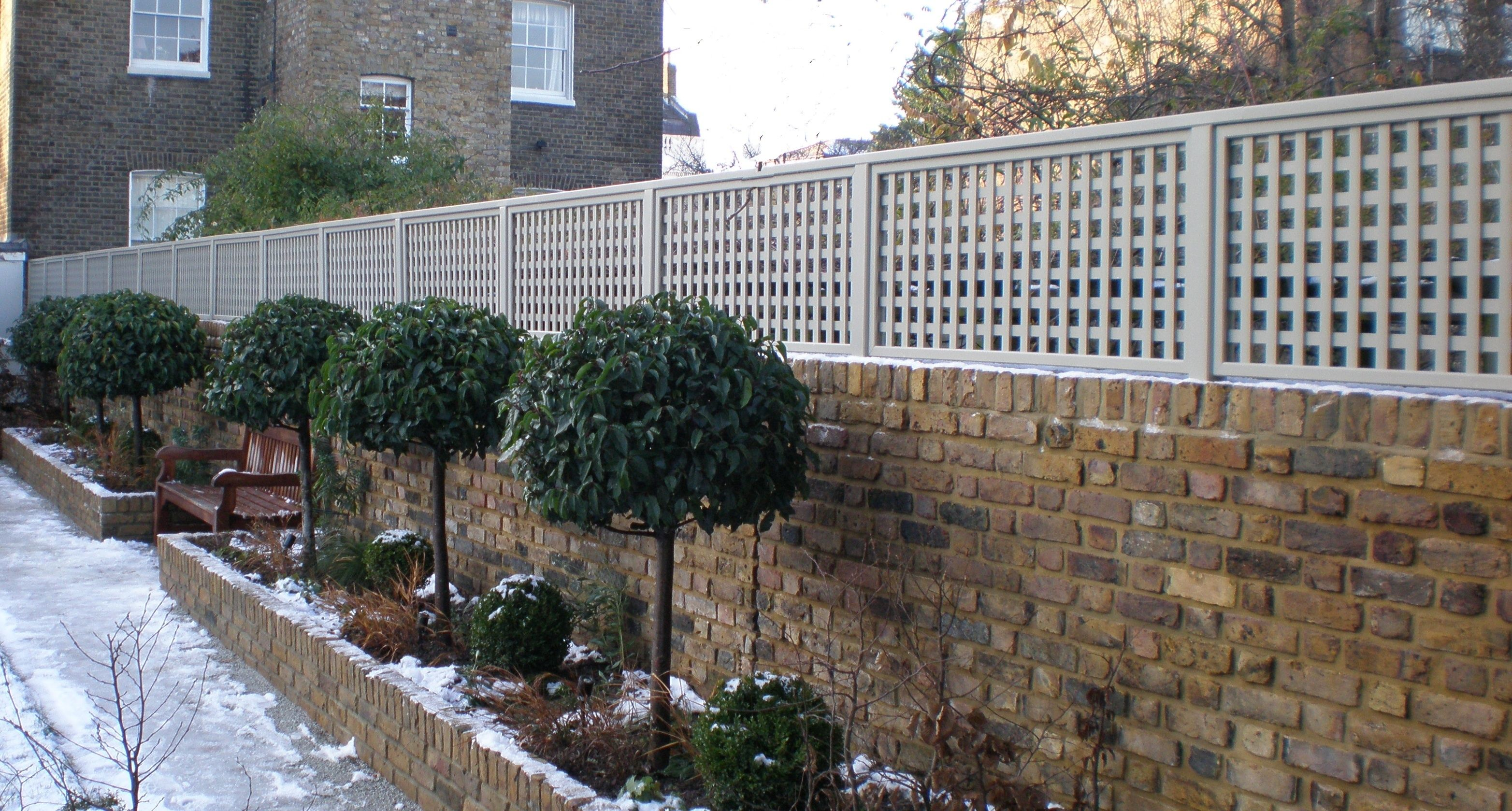 Garden bed with trees  trellis painted light grey on top of brick wall raised bed with