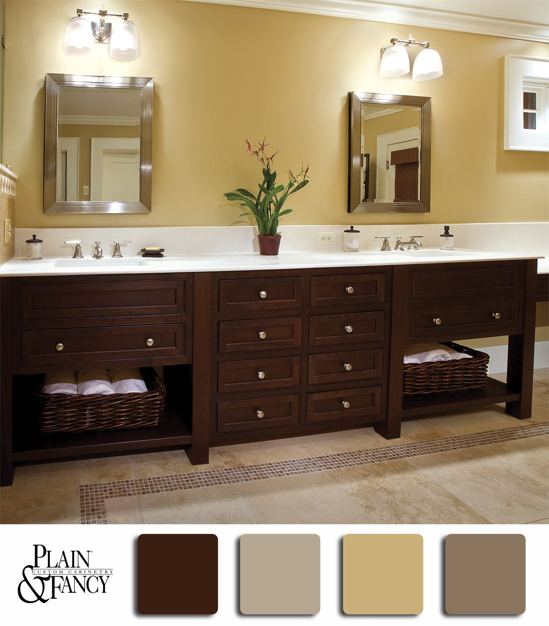 A Lovely Bathroom With A Brown Double Vanity With Yellow Creme