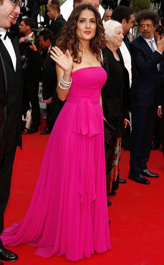 Salma Hayek adds a pop of color to the red carpet in a strapless bright raspberry gown by Saint Laurent.