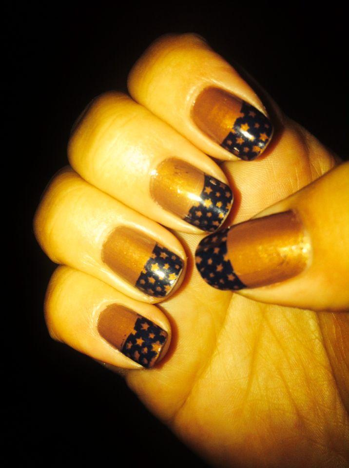Esmalte dorado con tip negro de estrellas hecho con Konad nail stamp.