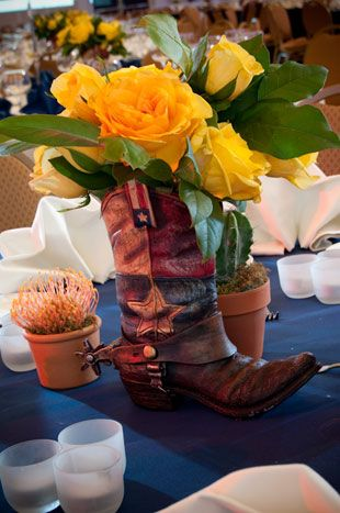 Custom-made centerpieces hold yellow roses. Real boots stuffed with newspaper make for easy-to-find thrift store centerpieces. Signs stuck in the middle serve as table names/numbers.