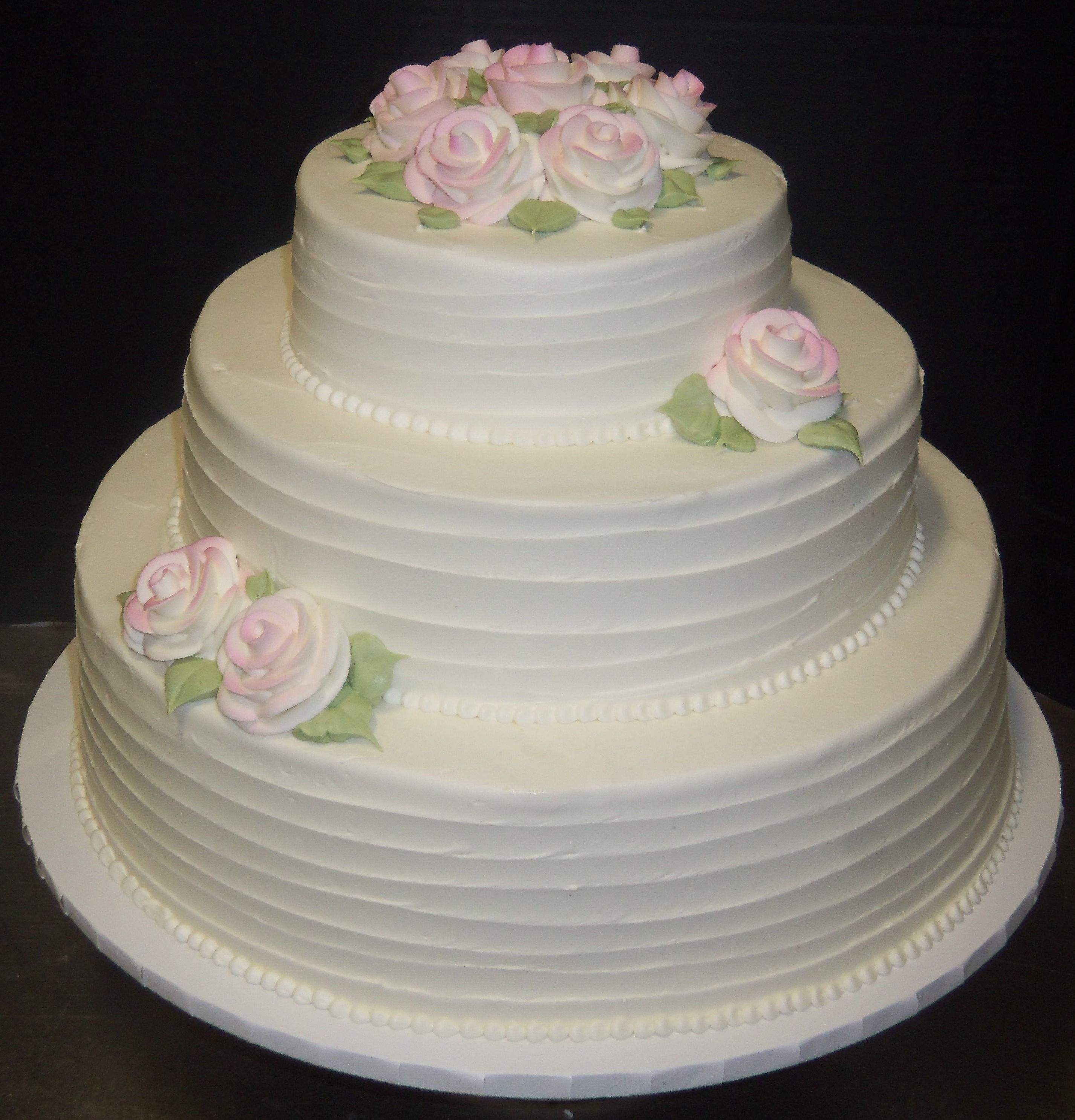 Pale pink roses decorate a three tier cake with horizontal line textures around the layers.