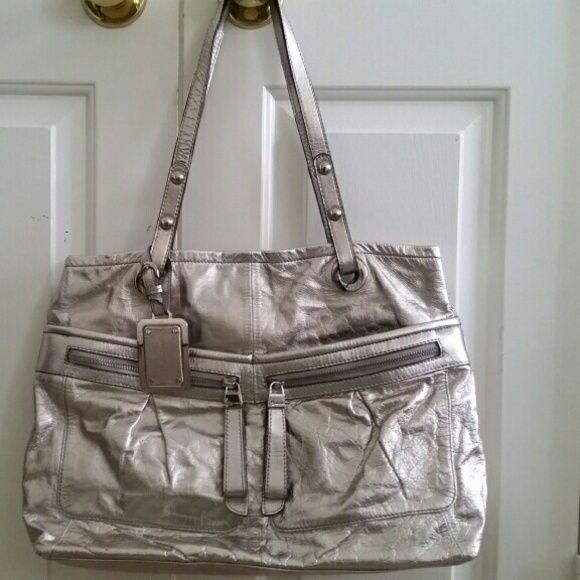 B. Makowsky Metallic Tote Bag GORGEOUS B. Mak bag! The exterior features metallic silver, crinkled leather, bold, silver tone hardware - incl. a giant, silver and leather hangtag, multiple pockets on front, and 2 straps. The interior features beautiful, soft, pale green, satin - like material, and has a large zippered pocket that divides the interior into 2 sections (one section has a zip pocket, 2 multifunction pockets, and a D ring). In like new condition! b. makowsky Bags Totes