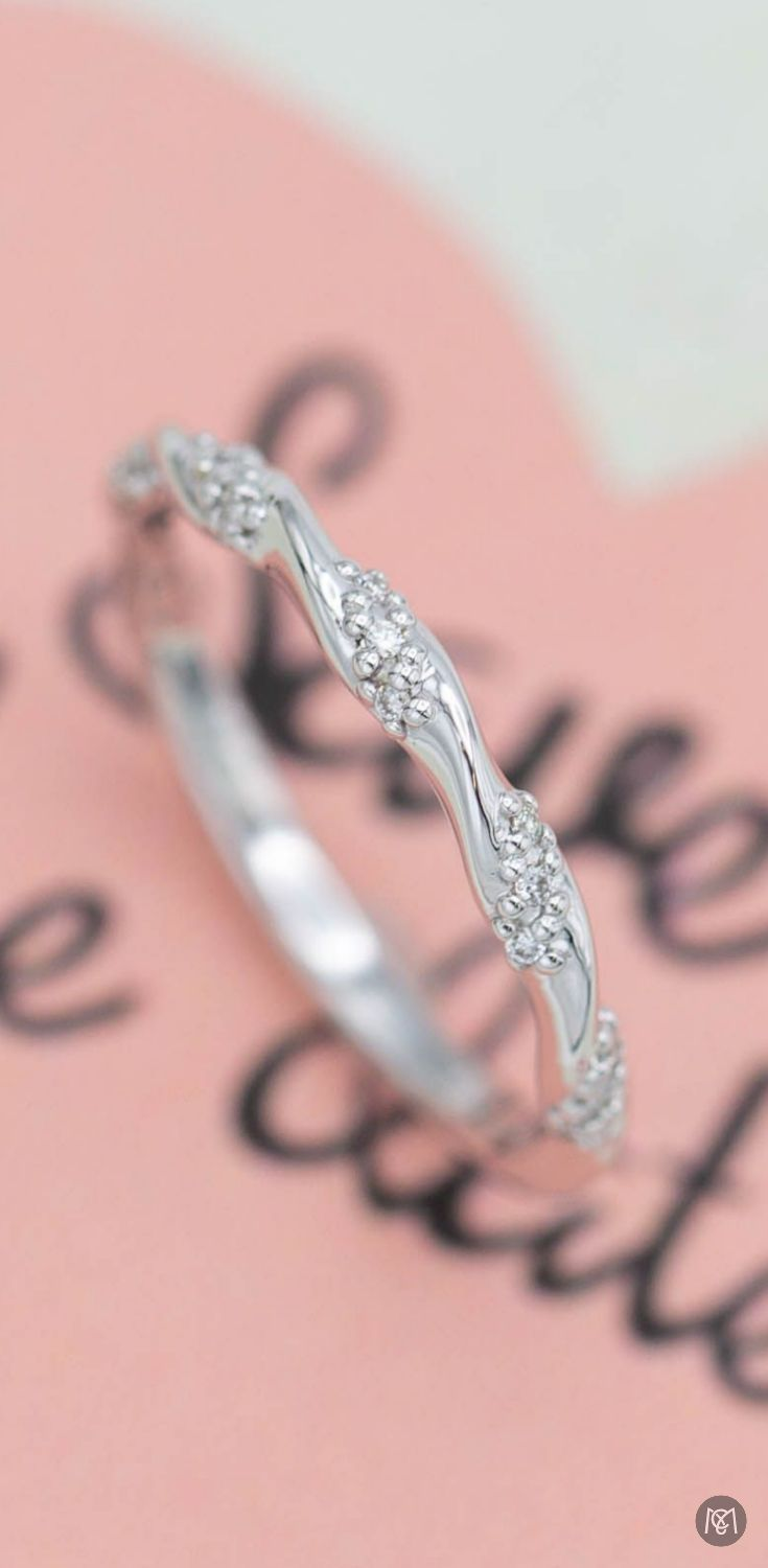 This delicate twisting diamond band would make a great stacking ring ...