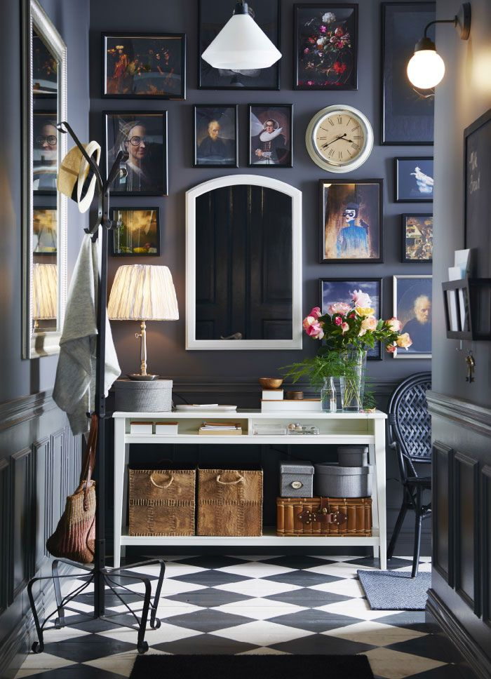 A small gray hallway with a white console table and a mirror. Shown ...