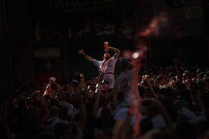 A man drinks wine to celebrate the official opening of the San Fermin festival in Pamplona, Spain