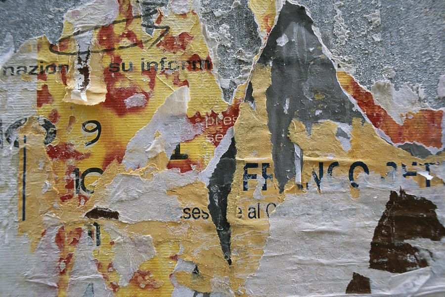 closeup of torn posters on a wall photograph