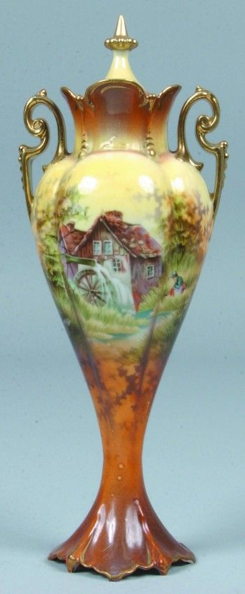 """RS Prussia Vase, 9""""h.; inverted tear drop shape with raised scallop base, 4 lobbed body with scalloped topped throat and scrolled handles. Brown to orange to yellow fade bottom to top with mill scene, gold handles and finial"""