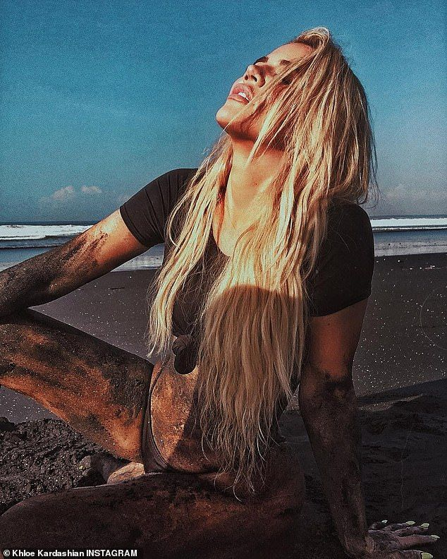 Khloe Kardashian gets dirty as she smothers herself in black sand