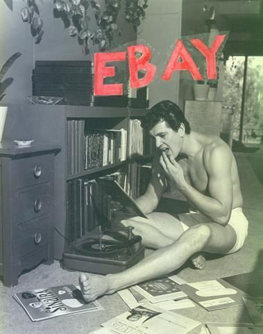 ROCK HUDSON BARECHESTED & BAREFOOT AT HOME WITH HIS RECORD COLLECTION