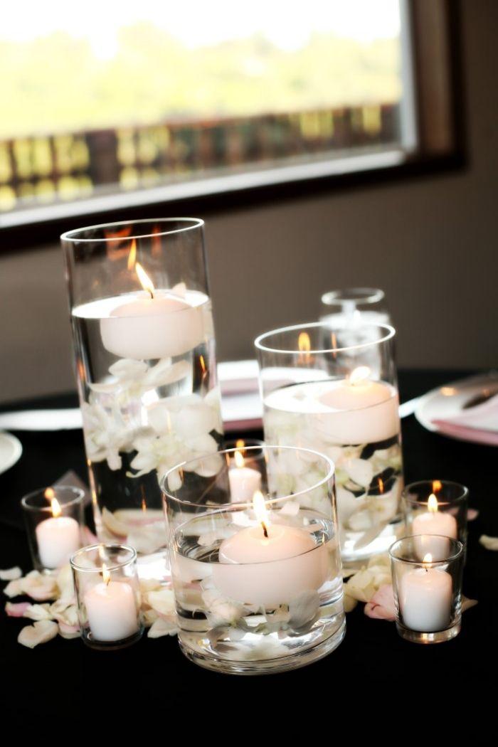 weiße Schwimmkerzen in runden Glasvasen und weiße Rosenblätter