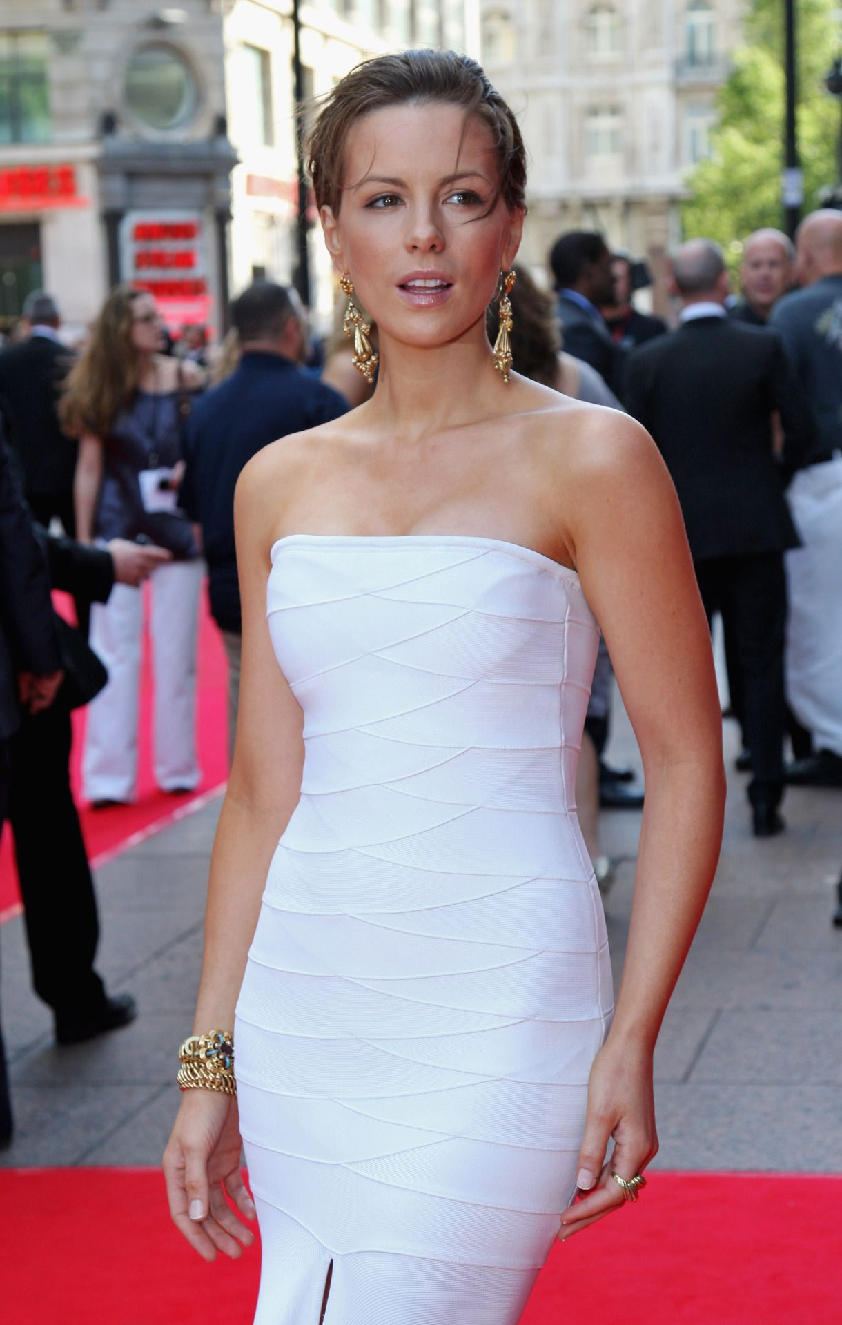 Kate beckinsale posing on the red carpet in a strapless white body