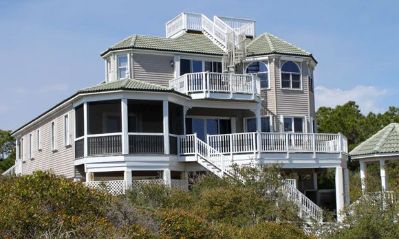 """Can't decide which kind of porch you like? Why choose? This home, called """"a Victorian dream,"""" has 'em all: a screened-in gazebo, a deck, a lanai — and even a widow's walk up top from which to wait for your sailor. The home is in a gated subdivision on a Gulf of Mexico barrier island off the Florida Panhandle, an area nicknamed the Forgotten Coast. Sitting on more than one acre one row back from the gulf, the home has no high-rise condominiums or structures in the way, so you can still get…"""
