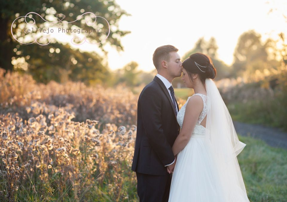 Wedding photography at Styal Lodge in Cheshire of a groom kissing the brides forehead during the golden hour.