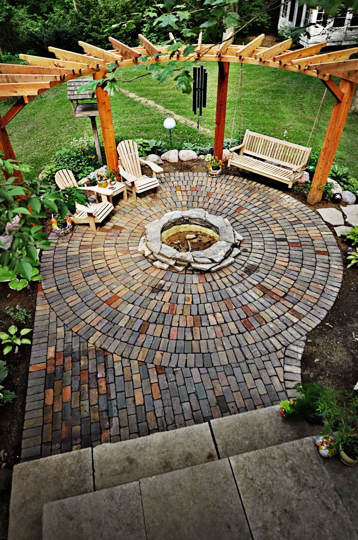 Curved pergola with fire pit. use flagstone instead of brick. Add shrubs  and/