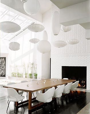 A Collection Of Bubble Lamps Hover Over This Dining Room Table Like White Clouds