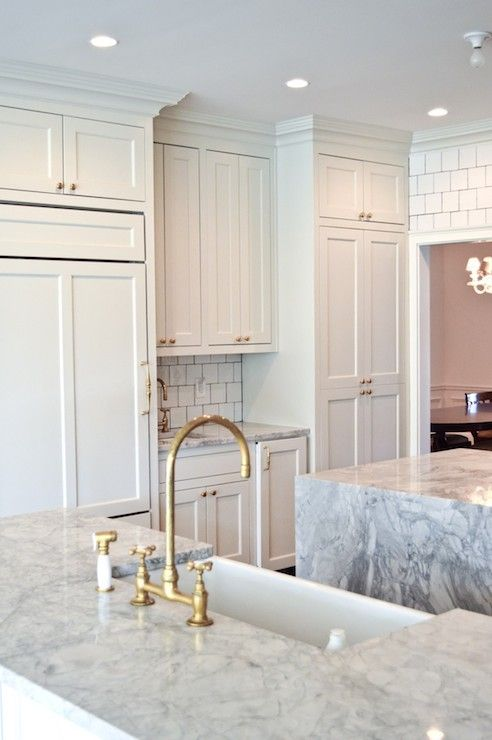 Beautiful Kitchen Features Off White Cabinets Accented With Brass Hardware Paired With Gray An Gray And White Kitchen White Quartzite Countertops Grey Kitchens