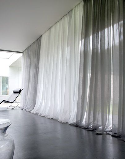 Modern window treatments pool the long drapes at the for Modern drapes window treatment