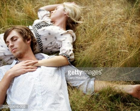 Couple Lying In Long Grass Eyes Closed Man Resting Head On Woman ...