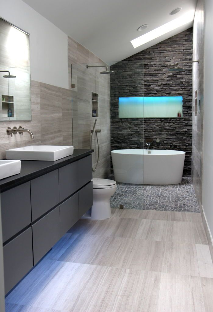 Amazing master bath retreat with dark stacked stone back wall feature and glass area for shower with dual shower heads and deep soaking tub. Modern master bathroom idea with dark custom cabinetry and top mounted sinks.