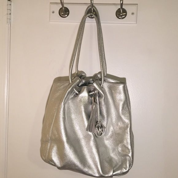 Michael Kors silver metallic tote bag Michael Kors silver metallic tote bag. Light wear and tear. Some scratches on emblem. Good condition. Price is firm here. Cheaper on merc Michael Kors Bags Shoulder Bags