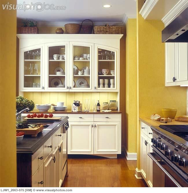 KITCHENS - Yellow walls with custom made off white cabinets, glass doors,  wood floor