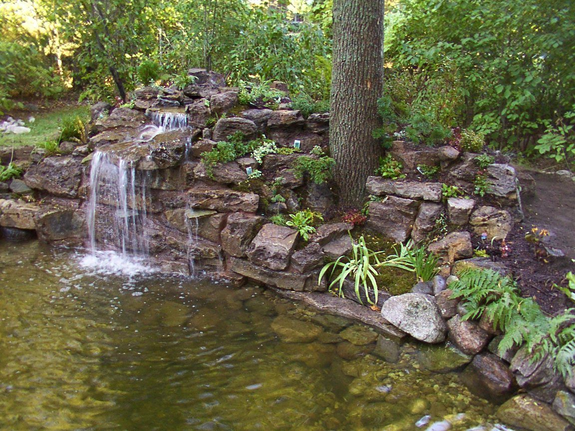 Backyard Waterfalls Ideas this pond with a stone waterfall is slightly off the beaten path of the yard Joans Idea For Rocks Against My Railroad Ties Beautiful Yard Plans Yahoo