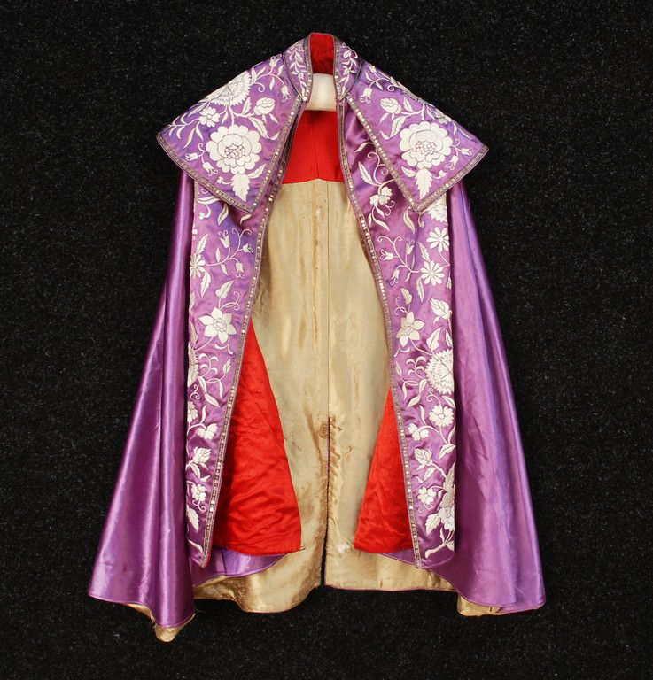 Spanish toreador cape with shawl and stand collars in lilac silk satin with white satin stitch floral and trimmed with narrow bands of sequins edged in gold metallic cord, vented back with diamond detail, red and platinum silk lining, 1900