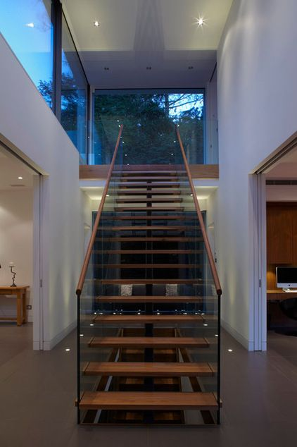 """The cantilevered staircase appears to float gently down from the floor-to-ceiling window on the landing upstairs, and is cleverly supported by a metal spine and glass balustrade."""