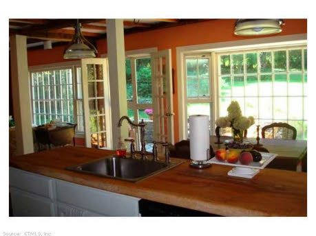 Open kitchen with lots of windows looking over backyard and gardens.  Find this home on Realtor.com