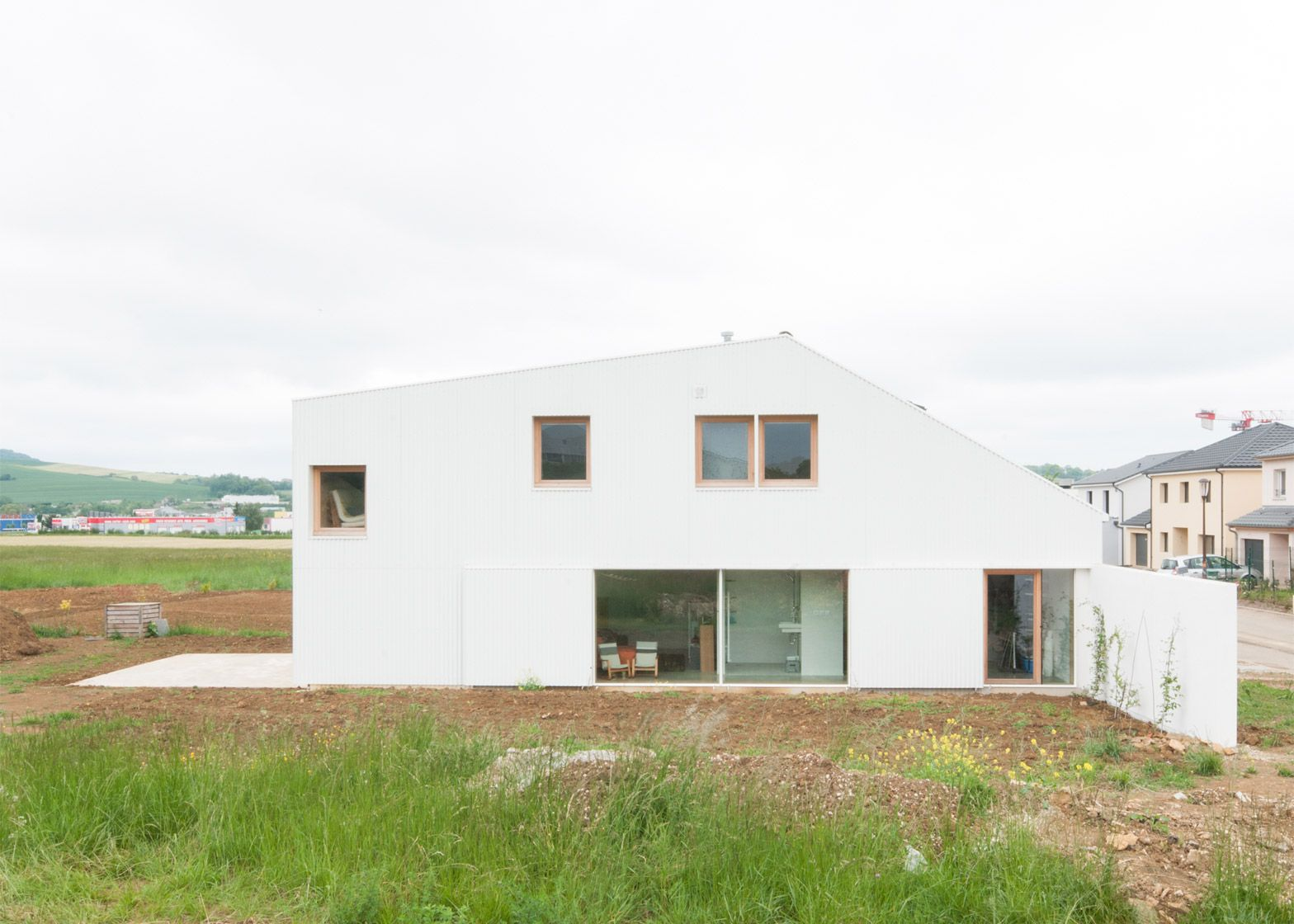 One half of this house by GENS is clad in corrugated plastic and has a chamfered corner